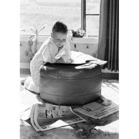 Boy leaning on hassock reading newspaper Poster Print