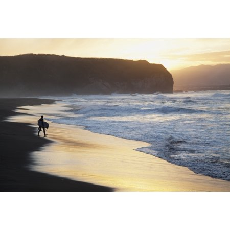 A surfer walks to the water at sunrise Santa Barbara Island Sao Miguel Island Acores Portugal PosterPrint