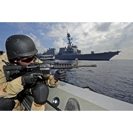 A soldier provides security in a rigid hull inflatable boat during a training exercise Poster Print