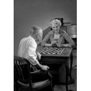 Mature couple playing board game Stretched Canvas -  (24 x 36)