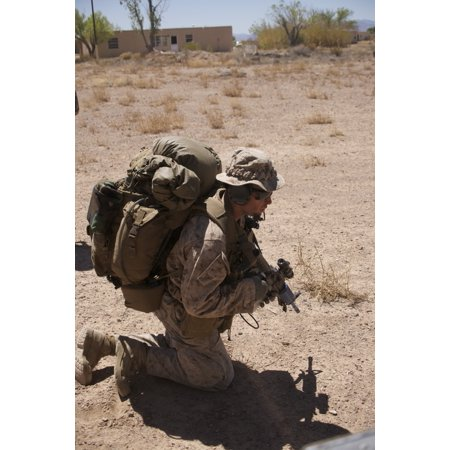 A US Marine pulls security while his team boards a UH-60 Black Hawk helicopter at Playas Training Area New Mexico during exercise Angel Thunder 2015 Poster Print