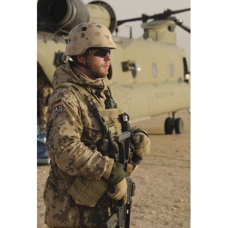 December 20 2010 - A German service member scans the horizon while standing guard near a US Army CH-47 Chinook helicopter in the Kunduz province Afghanistan Poster Print
