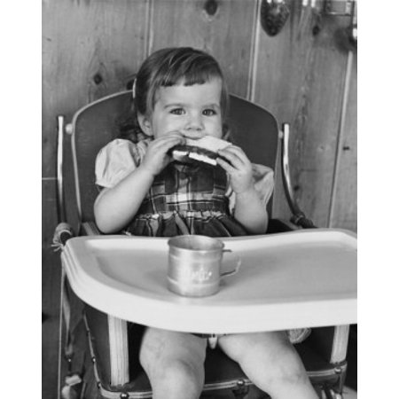 Baby girl sitting in a high chair and eating a slice of bread Canvas Art - (18 x 24)