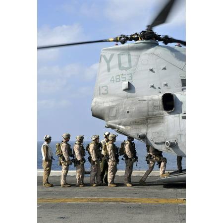 Arabian Sea January 12 2012 - Marines board a CH-46E Sea Knight helicopter on the flight deck of the amphibious assault ship USS Makin Island Poster Print