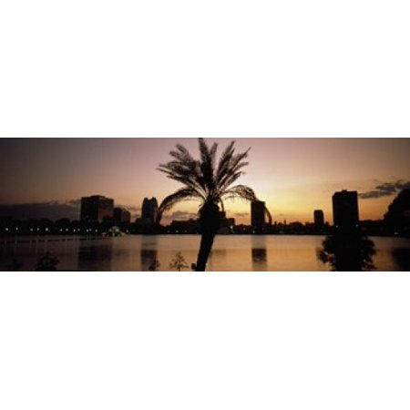 Silhouette of buildings at the waterfront Lake Eola Summerlin Park Orlando Orange County Florida USA Canvas Art - Panoramic Images (18 x