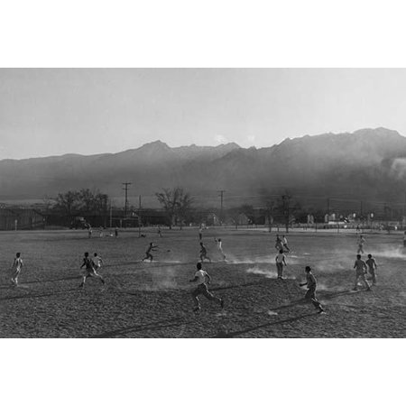 Players involved in a football game on a dusty field buildings and mountains in the distance  Ansel Easton Adams was an American photographer best known for his black-and-white photographs of the