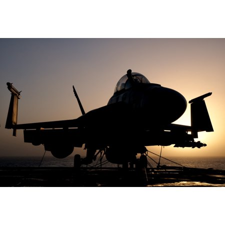 Silhouette of a US Navy FA-18E Super Hornet parked on the flight deck of aircraft carrier USS Nimitz off the coast of Pakistan Poster Print