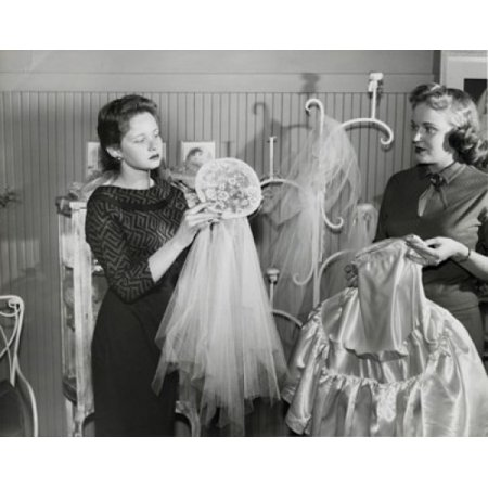 Mid adult woman with young woman holding dresses in clothing store Poster Print - Young Adult Stores