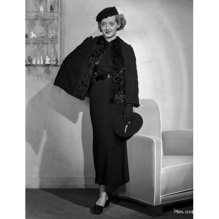 Bette Davis Posed Beside a Couch in Black Long Sleeve Lace Long Dress and Black Flat Cap Photo -