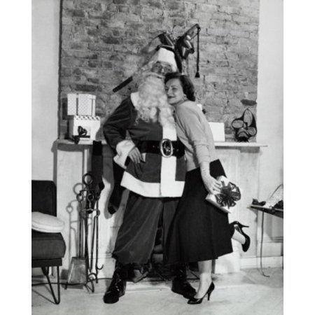 Side profile of a young woman holding a Christmas present and hugging Santa Claus in front of a fireplace Canvas Art -  (18 x 24)
