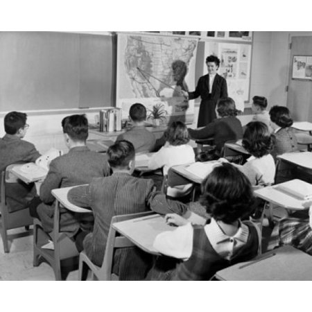 Female teacher pointing to a map in a classroom Poster Print