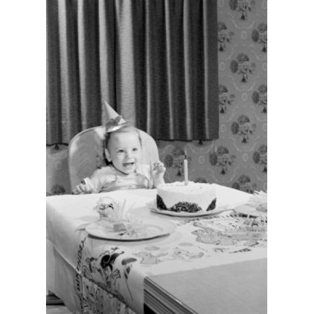 Baby girl wearing birthday hat sitting behind table with birthday cake Canvas Art - (18 x 24)