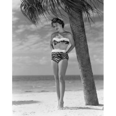 Pin-up girl standing under palm tree wearing bikini Canvas Art - (24 x 36)