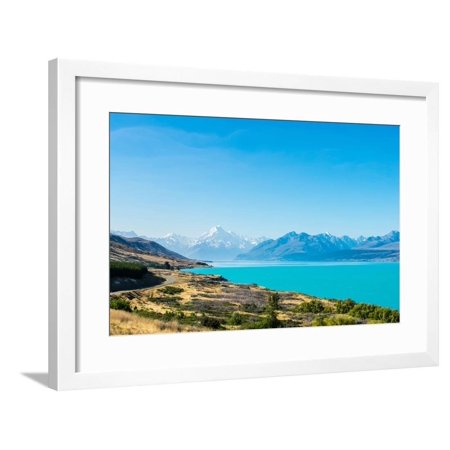 A road winds along the edge of a turquoise blue lake with mountains in the distance, New Zealand Framed Print Wall Art By Logan Brown (Logan Framers Edge)