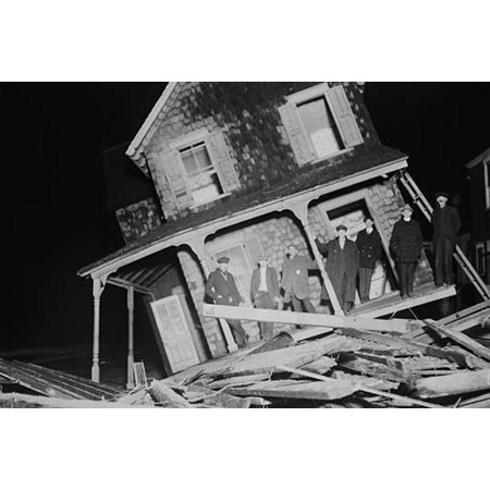 Men stand on Porch of a Sea bright Cottage torn from its foundation and tilted at a 45 degree angle.-Fine art canvas print (20