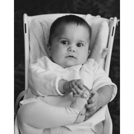 Baby girl sitting in a baby seat and holding her foot Canvas Art - (24 x 36)