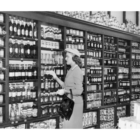 Side profile of a mid adult woman picking bottle from a shelf in a store Stretched Canvas -  (18 x 24) (Store Adult)