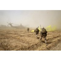 July 4 2014 - US Marines sprint across a field to load onto a CH-53E Super Stallion helicopter during a mission in Helmand province Afghanistan Poster Print