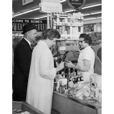 Mature couple standing at the checkout counter in a store Canvas Art -  (24 x