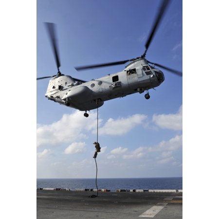 Arabian Sea January 12 2012 - A Marine fast ropes from a CH-46E Sea Knight helicopter onto the flight deck of the amphibious assault ship USS Makin Island Poster Print