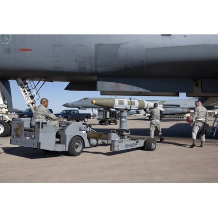 Weapons loaders from the 7th Bomb Wing prepare to load a GBU-31 JDAM onto a B-1 bomber at Dyess Air Force Base Texas Poster Print