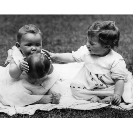 Two baby girls sitting on blanket and playing with ball Canvas Art - (24 x 36)