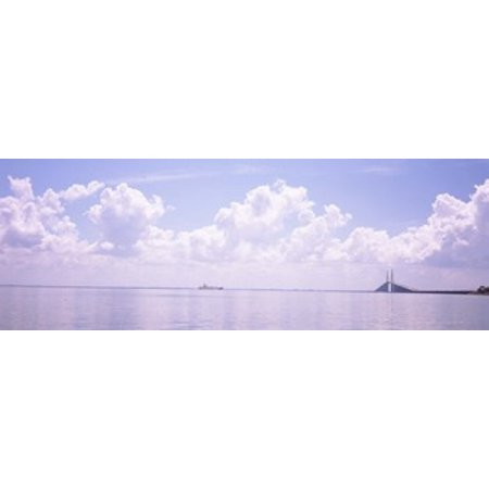 Sea with a container ship and a suspension bridge in distant Sunshine Skyway Bridge Tampa Bay Gulf of Mexico Florida USA Poster