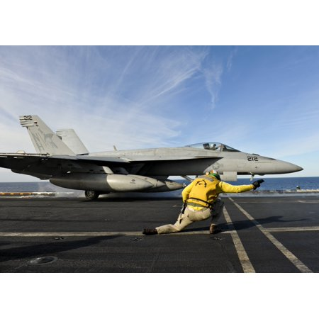 Pacific Ocean November 12 2012 - A shooter aboard the aircraft carrier USS Nimitz signals to launch an FA-18E Super Hornet from the ships flight deck Poster Print