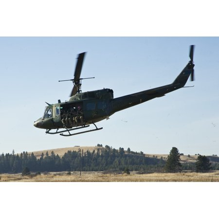 LAMINATED POSTER Members of the Survival, Evasion, Resistance and Escape School prepare to ascend on a UH-1 Huey heli Poster Print 24 x 36
