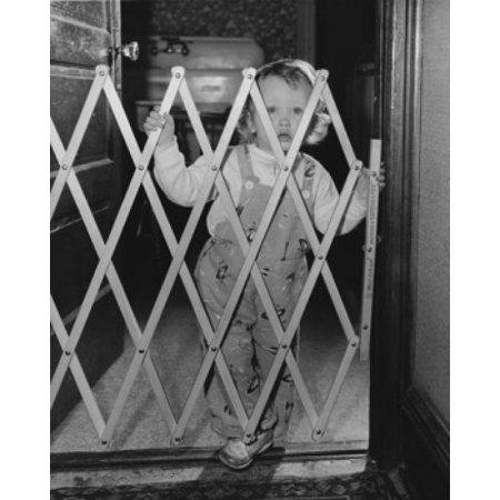 Baby girl standing behind a baby gate Canvas Art - (18 x 24)