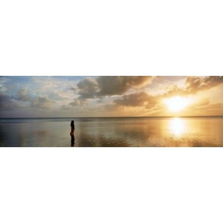 Woman standing on sandbar looking at sunset Aitutaki Cook Islands Poster Print