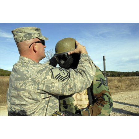 December 20 2007 - A Sergeant fits a protective mask to a students helmet before the final field training exercise Poster Print