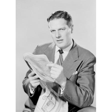 Studio portrait of businessman reading paper Poster Print