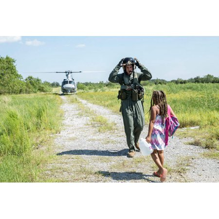 A US Marine leads a child to a UH-1Y helicopter during a Hurricane Harvey rescue mission Poster Print by Stocktrek Images