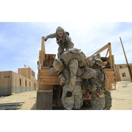 May 17 2014 - US Army Soldiers lift a simulated casualty during during Decisive Action Training Enviroment at the National Training Center Fort Irwin California Poster