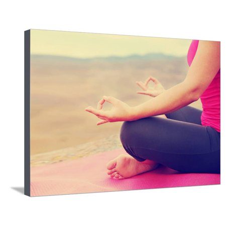 a woman meditating in a yoga pose on a hill top rock done