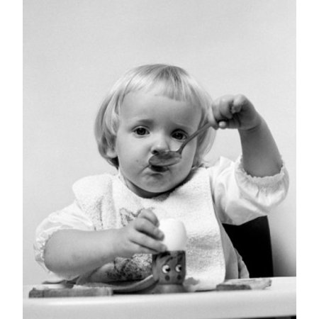 Baby girl with spoon eating egg Canvas Art - (24 x 36)