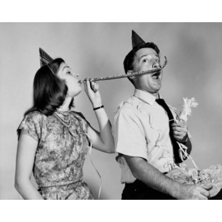 Young woman blowing a noisemaker near a young mans face Poster Print - Blow Up Noisemakers