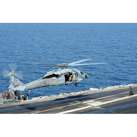 An MH-60S Sea Hawk helicopter lands on the flight deck of USS George HW Bush Poster Print by Stocktrek Images
