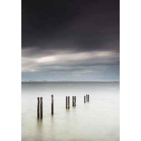 Post A Halloween Pic (Wooden posts in a row in the shallow water along the coast with a view of a city in the distance under dark storm cloudsSt marys bay northumberland england Canvas)