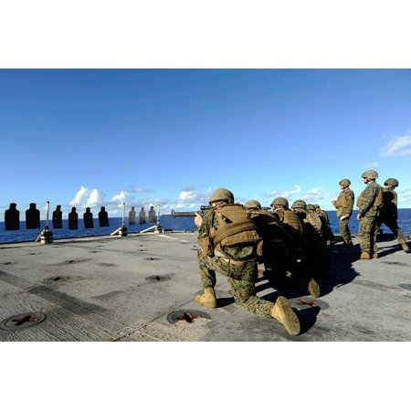 Marines practice shooting their M4 carbines and M16 rifles aboard USS Harpers Ferry Poster Print by Stocktrek -