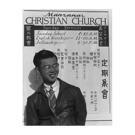 Tatsuo Miyake half-length portrait standing facing slightly right in front of a sign for church services in English and Japanese  Ansel Easton Adams was an American photographer best known for his