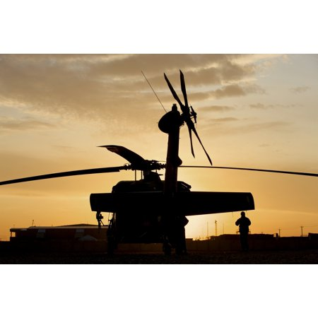 Gun Crew Stands - A gun crew member stands beside a UH-60L Black Hawk helicopter at Camp Liiberty Baghdad Iraq Poster Print