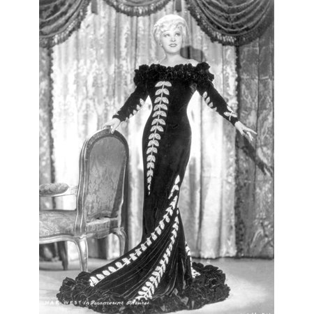 Mae West standing in Black Long Gown with Arm