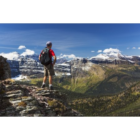 Male Hiker Standing On Top Of Mountain Ridge Overlooking Snow Peaked Mountains And Forest Valley Below With Blue Sky And Clouds Waterton Alberta Canada Canvas Art   Michael Interisano  Design Pics  19
