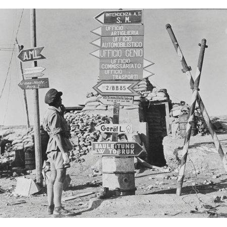 Sign posts printed in German and Italian at a street corner in Tobruk Libya circa 1942 Poster Print by Stocktrek Images