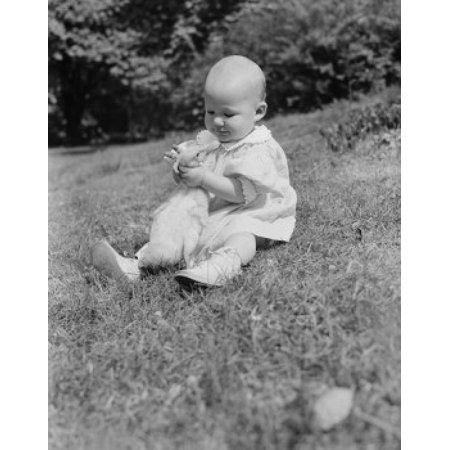 Baby girl sitting on grass hugging duck Canvas Art - (24 x 36)