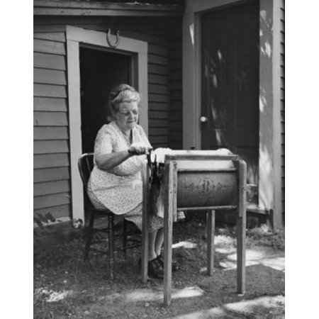 Senior woman churning butter in a butter churn Canvas Art - (24 x 36)