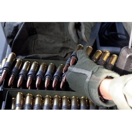 A soldier reaches for a belt of 50 caliber ammunition Poster Print by Stocktrek