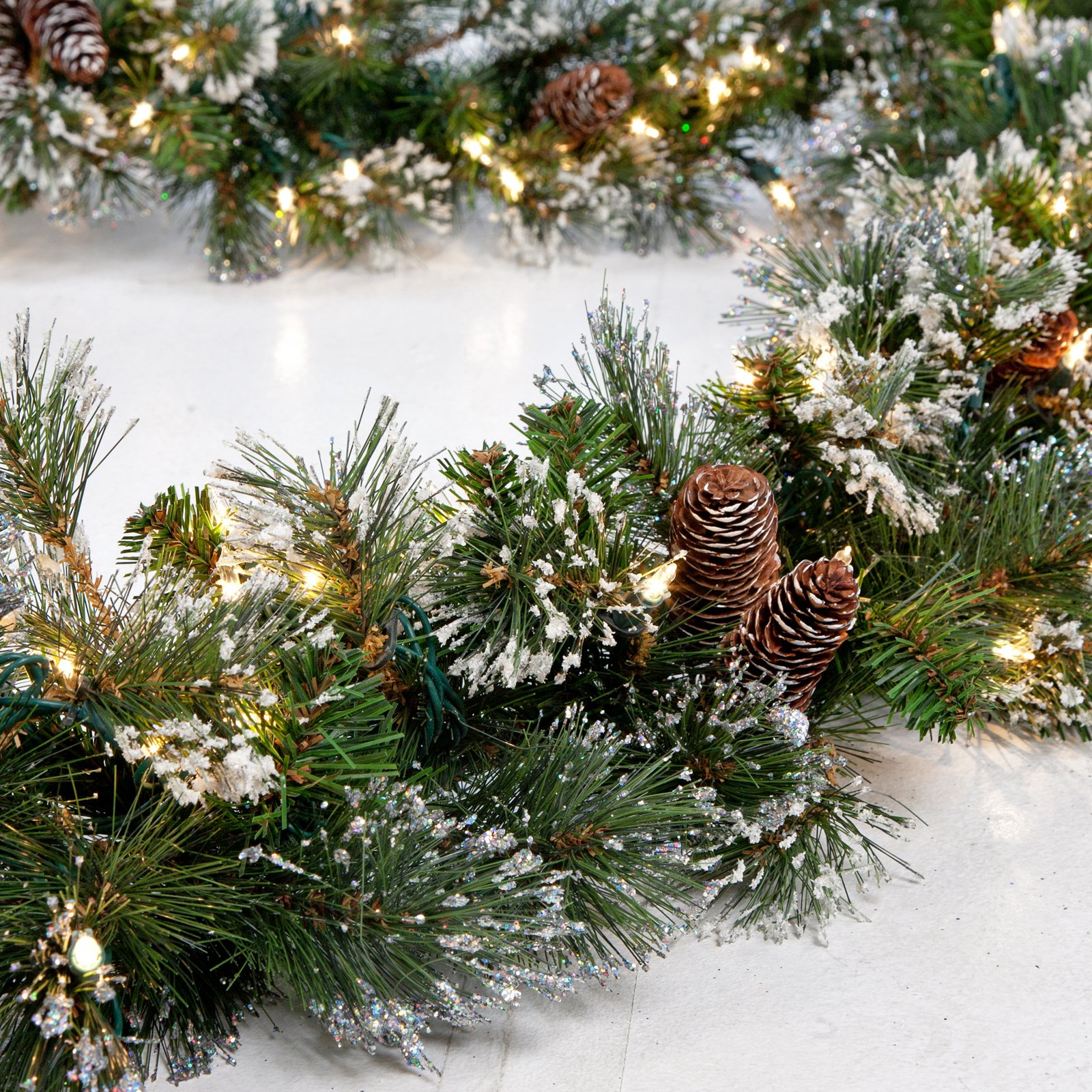 "National Tree 9' x 10"" Glitter Pine Garland with Cones, Snowflakes and 100 Clear Lights"